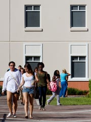 Florida Gulf Coast University students stroll through the commons area between residence halls in the South Village housing complex on Wednesday.