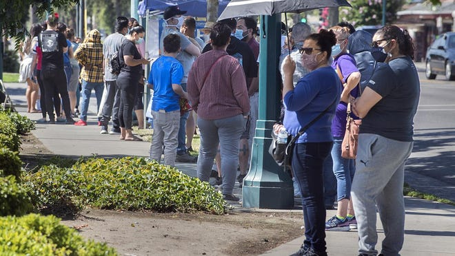 Hundreds of people wait at the back of the line along Cherokee Lane in front of Rancho San Miguel Market for COVID-19 testing. El Concilio and several partners will hold a free, drive through COVID-19 testing event on Friday at First Baptist Church in Lodi.