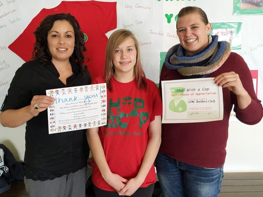 """Diana Aguirre, Builders Club President Rachel Bobo, and Sarah Sosa hold """"thank you"""" certificates after money raised by the La Plata Middle School Builders Club was donated to Shop With A Cop."""