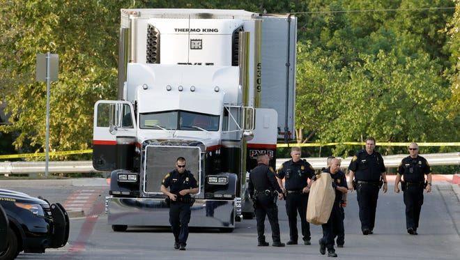 San Antonio police officers investigate the scene where eight people were found dead in a tractor-trailer loaded with at least 30 others outside a Walmart store in stifling summer heat in what police are calling a horrific human trafficking case in San Antonio.