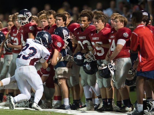 Trinity's Sam Farris (49) is pushed out of bounds by Montgomery Academy's Kevin Doh (23) during the game Friday, Sept. 23, 2016, at Trinity School in Montgomery, Ala.