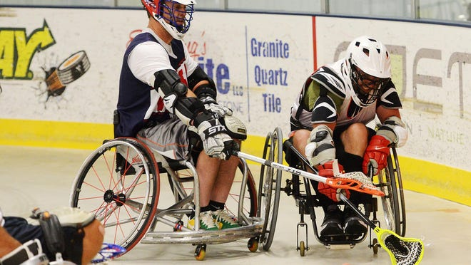 Bill Lundstrom of Wheelchair Lacrosse USA and Travis Robinson fight for the ball during a wheelchair lacrosse scrimmage Sunday at the Scheels IcePlex.