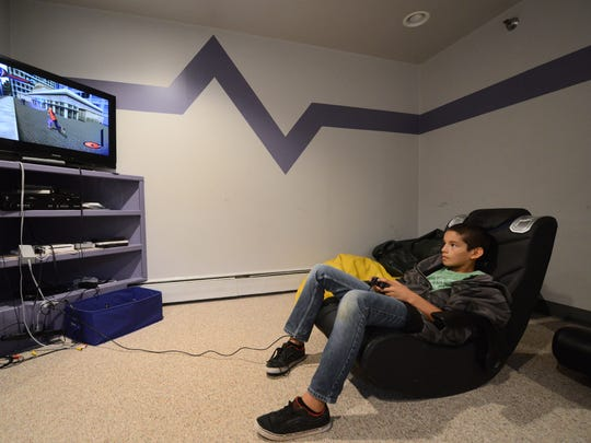 Tony Rivera plays Spider-Man on Playstation 2 in the evening after school in the teen room at Freedom House, where he lives, in Green Bay, Wis. on Monday, Sept. 22, 2014. Kyle Bursaw / Press-Gazette Media / @kbursaw