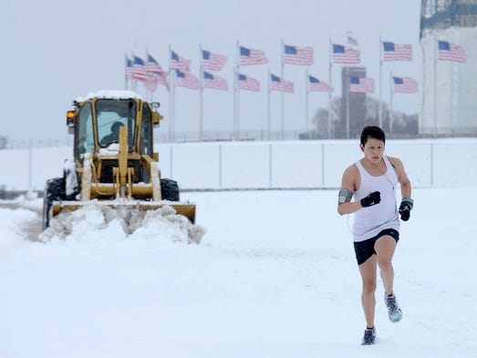 A jogger goes for a morning run in the snow on the grounds of the Washington Monument on March 17, 2014, in Washington, D.C. Snow covered parts of the Mid-Atlantic and Northeast as winter-weary motorists faced another potentially treacherous commute just days before the start of spring.