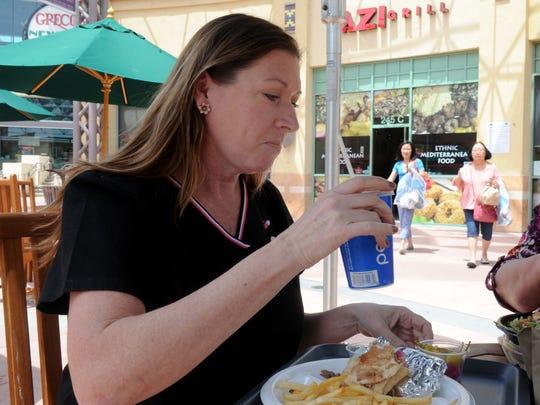 Sheri Perdomo eats a tri-tip/lamb wrap at Azi Grill