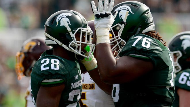 MSU offensive lineman Donovan Clark (76) pats running back Madre London (28) after a play in the fourth quarter of the Spartans' 30-10 win over Central Michigan.