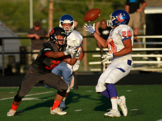 Aztec's Zane Bradshaw, left, makes a play on the ball against Los Lunas on Aug. 26 at Fred Cook Stadium in Aztec.