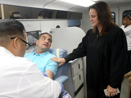 Judge Missy Medary talks with Nuece County Commissioner Brent Chesney as he donates blood Wednesday, Aug. 30, 2017, in Corpus Christi, Texas.