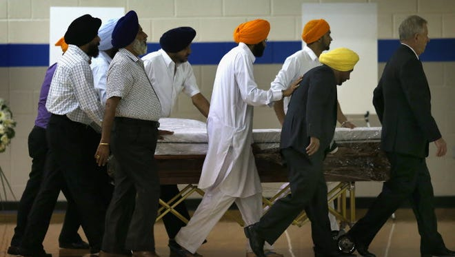 The remains one of the six people killed at the Sikh Temple of Wisconsin arrive for a memorial service, Oak Creek, Wis., Aug. 10, 2012.