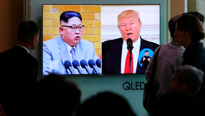 Commuters watch a TV screen showing file footage of Donald Trump, right, and North Korean leader Kim Jong Un during a news program at the Seoul Railway Station in Seoul, South Korea.