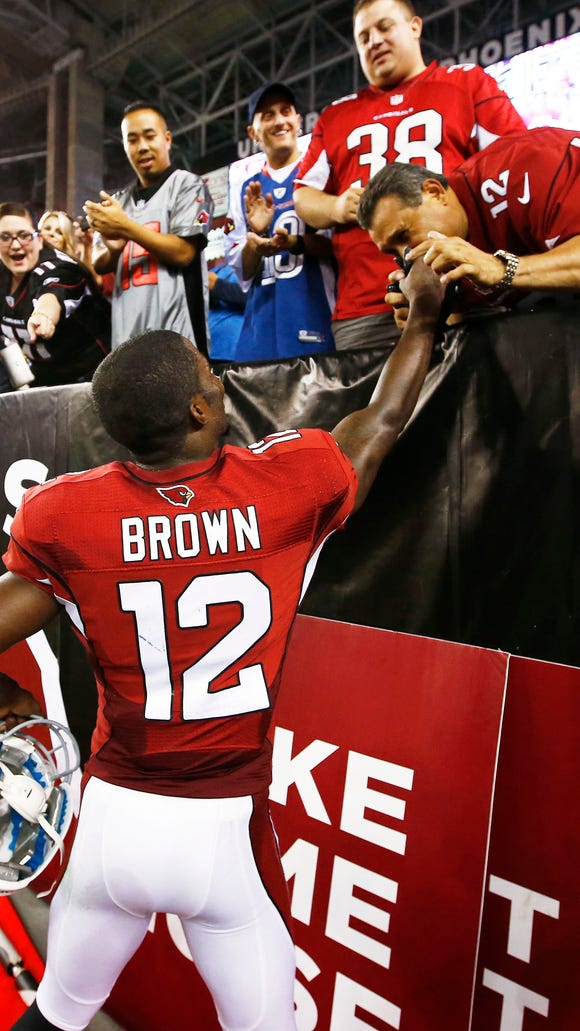 An Arizona Cardinals fan kisses the hand on rookie wide receiver John Brown after his game winning touchdown and first NFL TD against San Diego Chargers in the second half during Monday Night Football on Sep. 8, 2014 at University of Phoenix Stadium in Glendale, AZ. (Photo by Rob Schumacher/Arizona Republic)