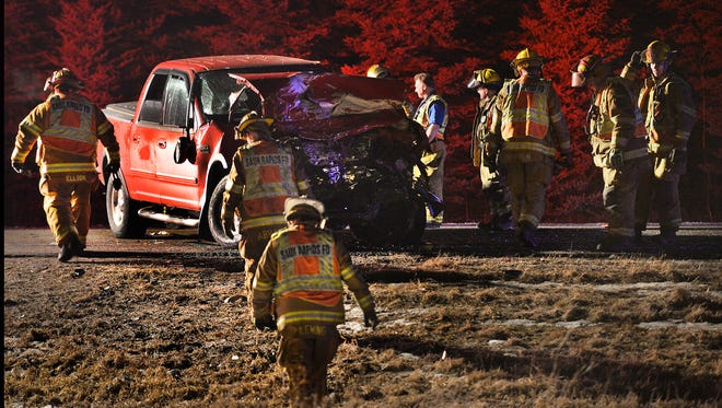 Sauk Rapids firefighters and other emergency personnel work at the scene of a head-on collision involving two pickup trucks Monday night near the intersection of Benton County Road 33 and 5th Avenue Northeast of Sauk Rapids.