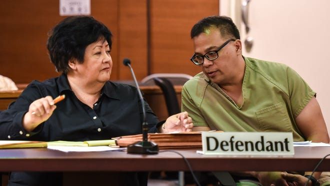 Former police officer Anthony Quenga, right, leans over to speak to his attorney, Sylvia Stake, during a resentencing hearing at the Superior Court of Guam on Wednesday, April 12, 2017. Quenga was convicted of several crimes, including first-degree criminal sexual conduct, kidnapping, felonious restraint and official misconduct, involving Blue House karaoke lounge employees, according to Pacific Daily News files. On Thursday, April 13, he was sentence to 30 years in prison.