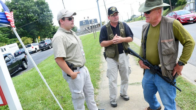 Bruce Cason and Mike Hall are armed with holstered handguns while Dave Beisner carries a  short barrel rifle. They maintain watch outside the Armed Forces Career Center on Richmond Road,  a task they volunteered to do as private citizens, in Staunton on Friday, July 24, 2015.