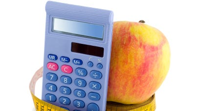 Apple with measuring tape calculator isolated on white background.
