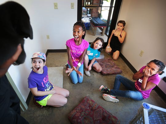 Mia Arredondo (left), Kaitlyn Lewis, Rylee Gillespie, Maret Roberts, and Maddi Iglesias react as volunteers from Target bring chubby black puppies into the room for the girls to play with during a one-day Kids Camp on Tuesday at the Collierville Animal Shelter.