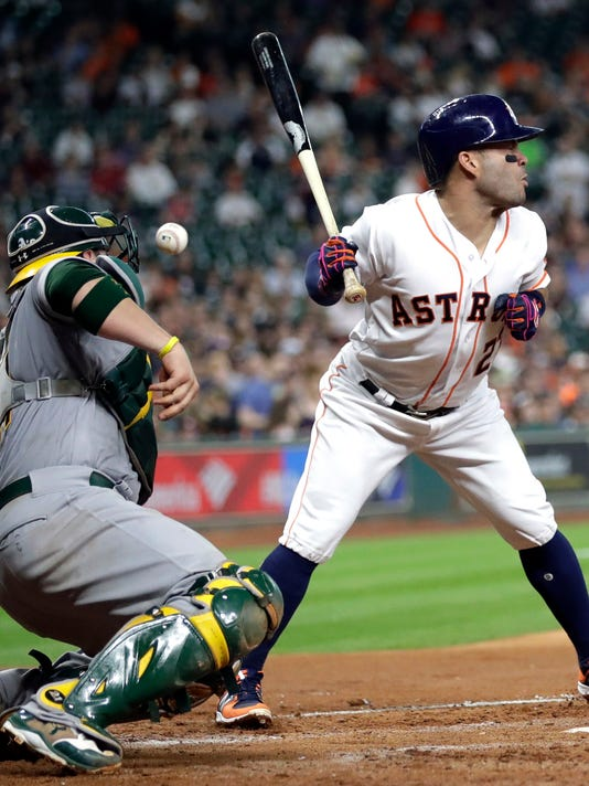 Houston Astros' Jose Altuve, right, is hit by a pitch thrown by Oakland Athletics starting pitcher Andrew Triggs as catcher Stephen Vogt, left, reaches for the ball during the third inning of a baseball game Saturday, April 29, 2017, in Houston. (AP Photo/David J. Phillip)