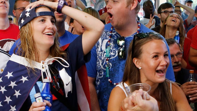 Soccer fans Ally Goodman, left, and Callie Pote, right, watch the U.S.-Germany World Cup match Thursday at Three Lions sports bar in Denver.