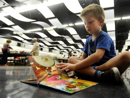 Andrew Gray, 4, reads one of his books while waiting