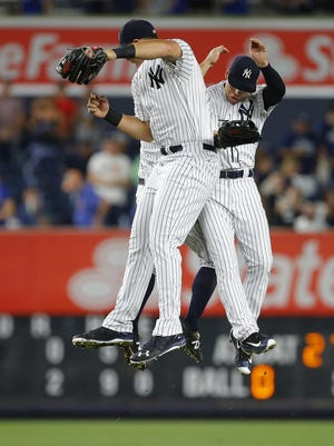NEW YORK, NY - SEPTEMBER 07: Outfielders Aaron Judge #99, Brett Gardner #11 and Jacoby Ellsbury #22 of the New York Yankees jump to celebrate their 2-0 win over the Toronto Blue Jays in a game at Yankee Stadium on September 7, 2016 in the Bronx borough of New York City. (Photo by Rich Schultz/Getty Images)