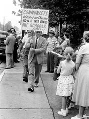 Segregationist Rev. Fred Stroud, center, of Bible Presbyterian Church on Monroe Street, leads a crowd of white people to protest integration at Buena Vista School Sept. 9, 1957.