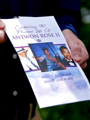 Kyle Fogarty shows the program for the funeral for