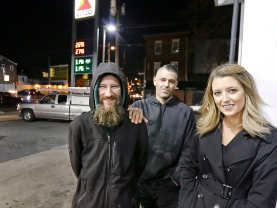 In this Nov. 17, 2017, photo, Johnny Bobbitt Jr., left, Kate McClure, right, and McClure's ex-boyfriend Mark D'Amico pose at a Citgo station in Philadelphia. When McClure ran out of gas, the homeless Bobbitt gave his last $20 to buy gas for her. They are facing conspiracy and theft charges after being arrested for raising more than $400,000 online at GoFundMe by using what the Burlington County prosecutor as said was a phony  story.