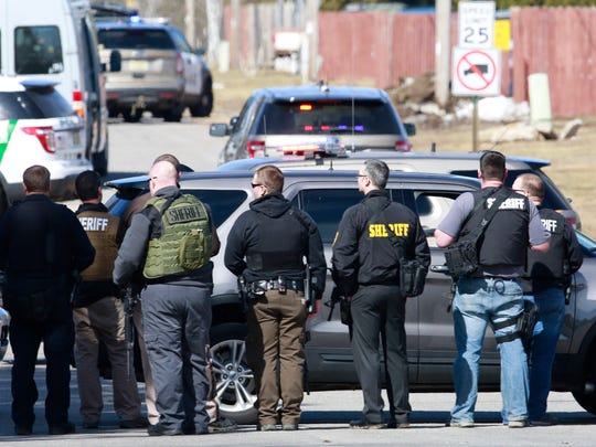 Police stand watch outside the site of a standoff Wednesday