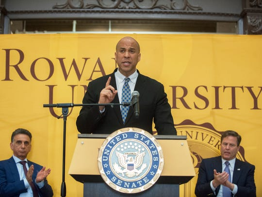 U.S. Sen. Cory Booker, center, speaks as Rowan President Ali Houshmand, left, and U.S. Rep. Donald Norcross, right, applaud during a press conference held at the Camden campus of Rowan University on Thursday to outline a major piece of legislation that would help address a national teacher shortage.