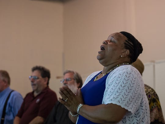 "The Rev. Roxie Dennis sings ""Amazing Grace"" while leading"