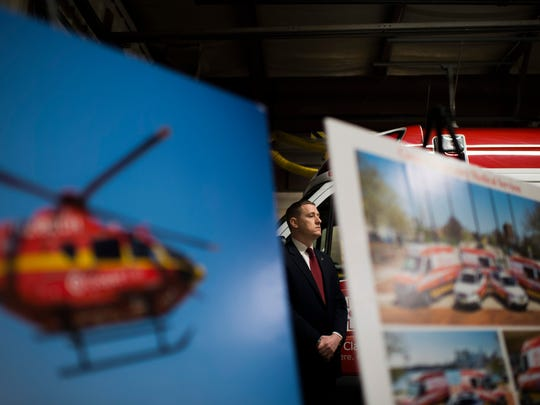 Posters on display inside the Cooper Emergency Medical Services ambulance bay during a press conference Tuesday in Camden.