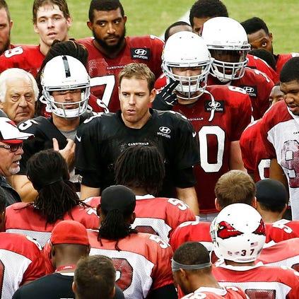 Arizona Cardinals huddle during training camp Wednesday, Aug. 20, 2014 at University of Phoenix Stadium in Glendale.