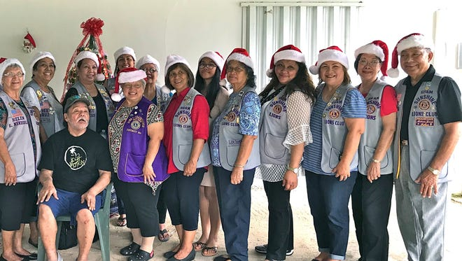 "Henry Santos, 61, (seated) of Agat, was the recipient of various supplies, supplements, song, and cheer from members of the Guam Sunshine Lions Club, whose mission is ""Caring for the Sick and the Elderly,"" on Dec. 16. Pictured are members and volunteers, from left: Lola Flores, Jill Pangelinan, Julie Garcia, Helen Mendiola, Dee Cruz, Clarice Quichocho, Tish Tano, Ewy Taitano, Helen Colby, Mary Taitano, Aubree Pangelinan, Dot Leon Guerrero, Lorraine Rivera, Julie Cruz, Marietta Camacho, and Pete Babauta."