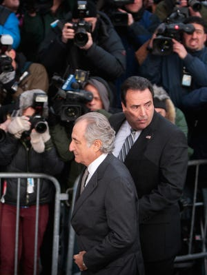Ponzi scheme architect Bernard Madoff passes news photographers while arriving at Manhattan federal court March 12, 2009