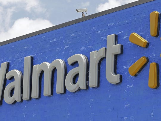 FILE - This June 1, 2017, file photo, shows a Walmart sign at a store in Hialeah Gardens, Fla. Walmart is rolling out next-day delivery on its most popular items, raising the stakes in the retail shipping wars. The nation's largest retailer says Tuesday, May 13, 2019, it's been building its own network of more efficient e-commerce distribution centers to enable the faster delivery. (AP Photo/Alan Diaz, File)