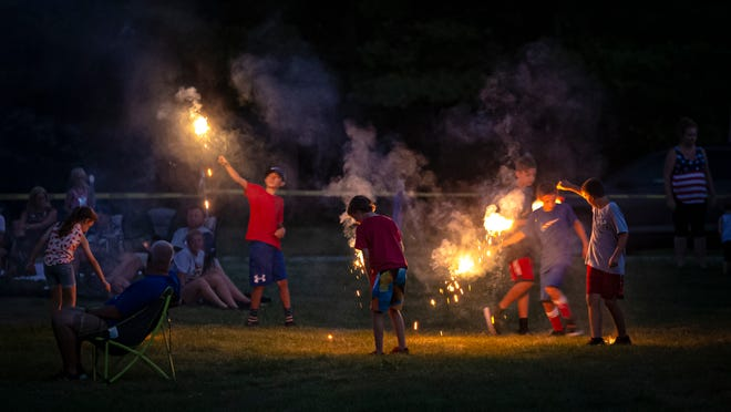 Youngsters run in circles as they play with sparklers as they wait for the fireworks show at Pleasant Plains High School, Friday, July 3, 2020, in Pleasant Plains, Ill.