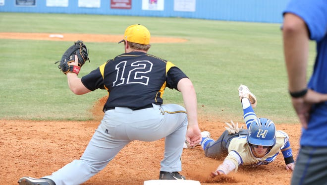 Trenton Peabody's Hunter Hudson looks to make a play on a Huntingdon player sliding back into first base in the Region 7-A championship on Wednesday at Huntingdon.
