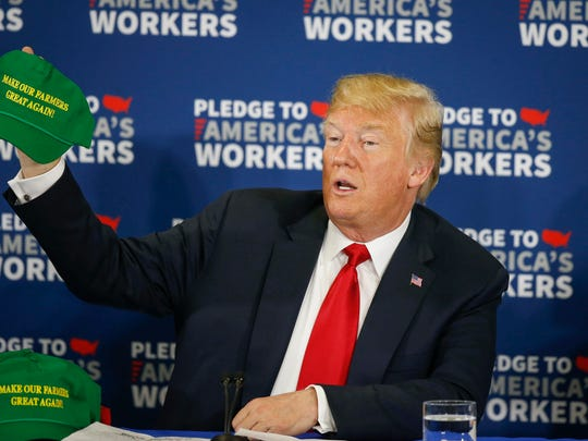 """President Donald Trump holds up a green """"Make Our Farmers Great Again"""" hat as he visited with eastern Iowa community leaders on Thursday, July 26, 2018, during a roundtable discussion at Northeast Iowa Community College in Peosta. Bryon Houlgrave/The Register"""