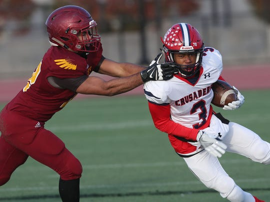 Stepinac's Shawn Harris (3) breaks away from Cardinal Hayes' Couri Baker (72) on a first half run during the CHSFL AAA semifinal at Macombs Dam Park in the Bronx Nov. 11, 2017. Stepinac won the game 13-12.