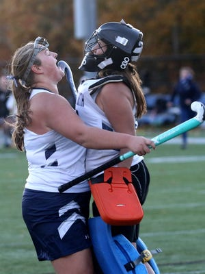 Rachel Motyka (left) and Maeve Tierney celebrate a win for the Plymouth North field hockey team.