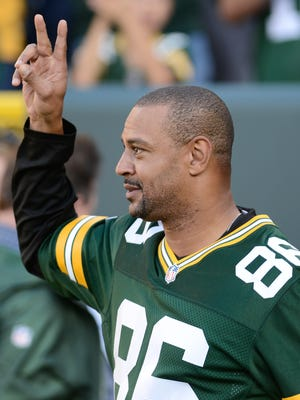 Antonio Freeman greets the crowd as he is introduced at halftime of the Packers' Week 2 game against the Jets in 2014.