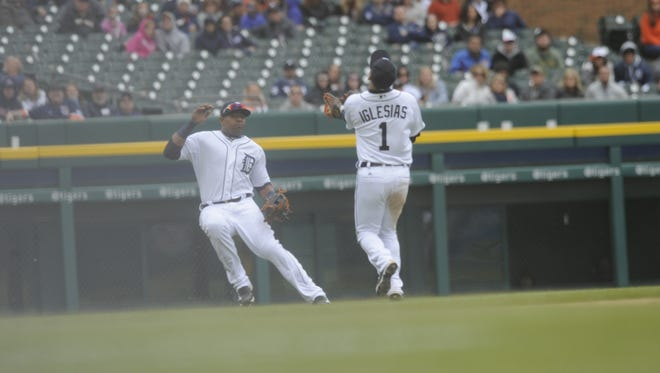 Tigers outfielder Yoenis Cespedes (52) and shortstop Jose Iglesias (1) go after a flyball by the Indians' Mike Aviles (4) in the ninth inning Sunday at Comerica Park.