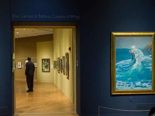 Gerret Copeland looks around the Delaware Art Museum, which his grandmother founded and his father helped run and support. The two paintings in the foreground were done by illustrator Howard Pyle.