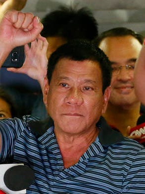 FILE - In this April 22, 2016 file photo, then-presidential candidate Mayor Rodrigo Duterte clenches his fist during a campaign sortie at Silang township, Cavite province south of Manila, Philippines.