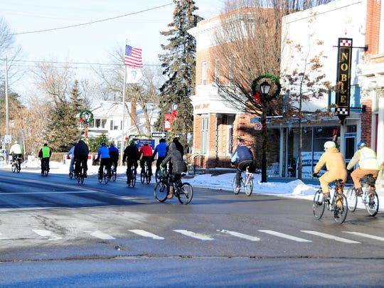 Cyclists take off west on Huron Avenue toward Croswell as part of the annual New Year's Day bike ride on Jan. 1, 2018, in Lexington, Michigan.