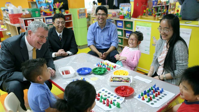New York Mayor Bill de Blasio, left, and City Council member Carlos Menchaca, third from left, visit a prekindergarten class at the Brooklyn Chinese American Association Early Childhood Education Center in Brooklyn  in May.