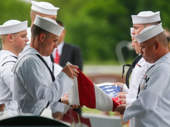 Members of the United States Navy Honor Guard remove