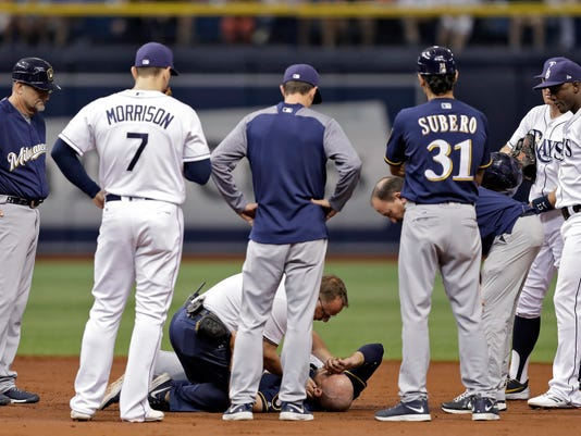 Players and coaches watch as a trainer helps Milwaukee Brewers' Travis Shaw after he was hit with a throw while stealing second base during the second inning of a baseball game Saturday, Aug. 5, 2017, in St. Petersburg, Fla. Shaw left the game. (AP Photo/Chris O'Meara)