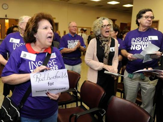 Ellen Scudder and others sing songs during an Insure