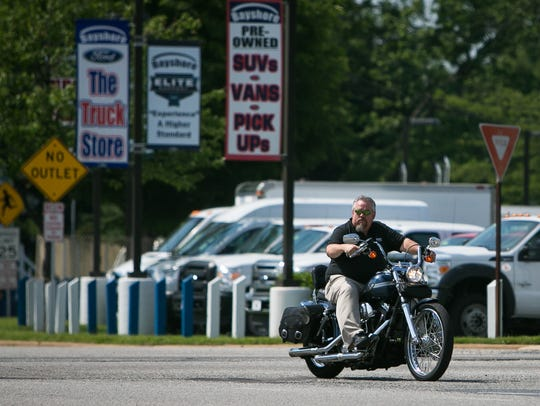 A motorcyclist rolls through the intersection of Memorial